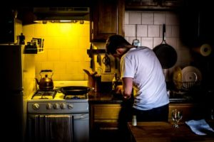 Man standing in kitchen.