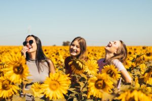 Women in a sunflower field, happy
