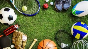 An assortment of all sports gears placed circularly on a grassy field, including a tennis racket, football, baseball gloves, etc