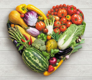 Essential fruits and vegetables placed in a beautiful heart shape on a wooden surface, teaching you to eat healthy is the nutrition group on Hala Yalla
